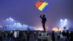 Ein Mann steht auf einer Erhöhung und schwenkt eine rumänische Flagge.