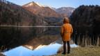 Ein Mann im Anorak steht an einem Bergsee