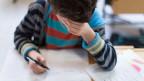 Ein Junge löst eine Schulaufgabe und fasst sich angestrengt an die Stirn.