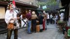 Ein Mann mit einem Dudelsack auf einem Mittelaltermarkt.