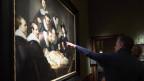 Ein Bild von Rembrandt hängt an einer schwarzen Wand. Ein Mann zeigt mit ausgestrecktem Arm und Zeigefinger auf ein Detail des Bildes.