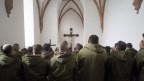 Man sieht Männer sitzend von Hinten. Alle Tragen eine Militärgrüne Jacke. Vorne an der Wand hängt ein Kreuz mit Jesu.