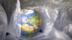 Ein kleiner Globus ist verpackt in Plastik