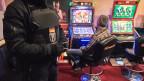 Eine Bar, in der ein Mann an einem Spielautomaten sitzt. Neben ihm steht die Polizei, die eine Razzia durchfürht.