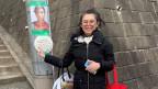 Frau mit grosser, runder Brille in Mantel und mit Taschen um den Arm steht vor einer Steinwand und lächelt in die Kamera.
