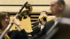 Blick ins Orchester: Man sieht eine Posaune von vorne, und ganz verschwommen Kontrabassisten.,