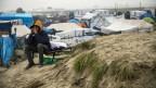 Ein Mann mit Kapuze über dem Kopf sitzt auf einer alten Sonnenliege vor einem Meer an improvisierten Zelten.