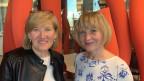 Zwei Frauen mittleren Alters stehen vor einer Säule und lächeln in die Kamera.