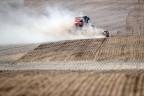 Ein Traktor zieht eine Drillmaschine auf einem Feld hinter sich her