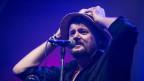 Ein Mann vor einem Mikrofon greift sich an seinen Hut