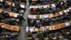 Einen Blick in den Nationalratssaal von oben auf Tische, Stühle und PolitikerInnen