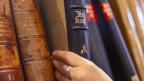 Eine Hand greift nach einem Buch