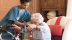 Eine Pflegerin hilft einer sitzenden Frau am Rollator