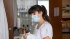 Eine Krankenpflegerin steht an einem Spitalbett