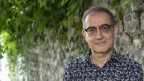 Ein grauhaariger Mann mit Brille vor einer Mauer