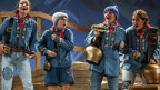Vier Mädchen stehen auf der Bühne, blau gekleidet mit Glocken