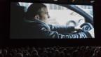 Kinobesuchende sitzen vor einer bespieltenLeinwand