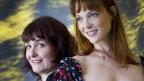 Zwei Frauen vor der Kamera, eine blickt in sie