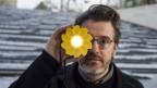 Ein Mann mit Bart und Brille hält ein leuchtendes Objekt vor sein rechtes Auge