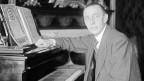 Rachmaninow mittleren Alters sitzt vor einem Klavier und schaut in die Kamera