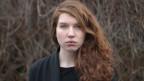 Junge Frau mit langen roten Haaren blickt in die Kamera