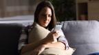 Frau sitzt auf der Couch und blickt enttäuscht auf ihr Handy