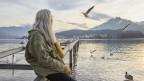 Frau mit langen, grauen Haaren sitzt am See und schaut in die Ferne