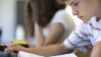 Junge im Teenager alters sitzt an einem Pult und blickt konzentriert auf ein Blatt vor sich