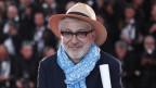 Älterer Mann mit grauen Haaren, Hut, Brille und Schal vor einem Publikum im Hintergrund