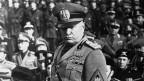 Schwarz- weiss Foto eines Mannes in Uniform vor einer Truppe in Uniform