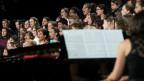 Blick auf ein Klavier, im Hintergrund ein Chor