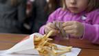 Mädchen sitzt am Tisch mit einem Teller Pommes Frittes vor sich