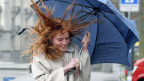 Frau mit roten langen Haaren und Regenschirm im windigen Wetter