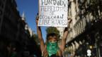 Frau an einer Demonstration hält Schild in die Höhe