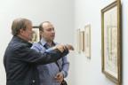 Blinder Mann vor einem Gemälde, ein weiterer Mann steht neben ihm