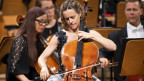 Frau in grauem Kleid spielt Cello vor einem Orchester auf der Bühne