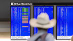 Ein Mann mit Hut vor einer Abflugtafel im Flughafen Zürich Kloten