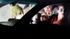 Vier geschminkte Frauen sitzen in einem Auto.