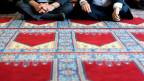 Männer sitzen auf Teppich.