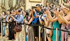 Eine Menschenmenge steht fotografierend vor alten Meistern.