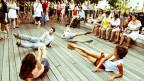 Tänzer räkeln sich auf einem Holzboden im Freien.