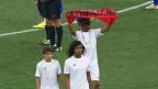Ein Guarani läuft mit zwei Kindern über ein Spielfeld in Brasilien. Er hält ein Spruchband mit dem Titel «Grenzziehung jetzt» («Demarcação já»).