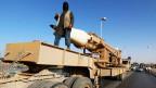 Ein maskierter Mann steht auf einem Fahrzeug, das eine grosse Rakete mit sich führt.