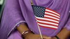 Eine dunkelhäutige Frau in lila Gewand hält eine kleine USA-Flagge in den Händen.