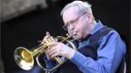Kenny Wheeler bläst in eine Trompete.