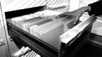Eine Hand greift in eine Aktenschublade, in die viele Unterlagen gehängt sind.