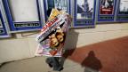 """Ein Mann hängt ein Plakat des Films """"The Interview"""" ab."""