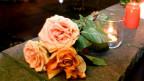 Blumen und Kerzen auf einem Mäuerchen