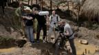 Milo Rau und andere Menschen mit Kameras und Aufnahmegeräten im Kongo.
