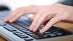 Hände auf eine Computer-Tastatur.